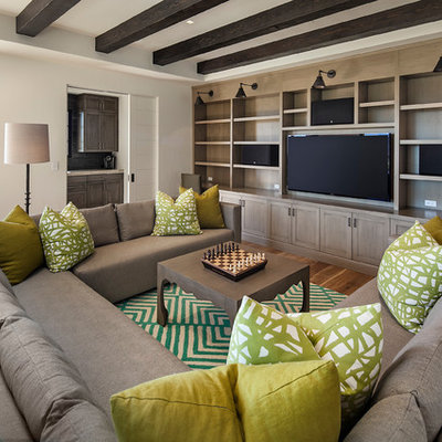 Example of a large trendy enclosed medium tone wood floor family room library design in Santa Barbara with white walls and a media wall