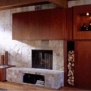 Idée de décoration pour une grand salle de séjour design fermée avec une cheminée standard, un manteau de cheminée en pierre, un sol en bois clair, un mur beige, un téléviseur dissimulé et un sol beige.