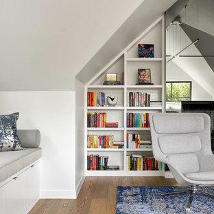 Cette image montre une grand salle de séjour avec une bibliothèque ou un coin lecture design fermée avec un mur blanc, un sol en bois brun et un sol vert.