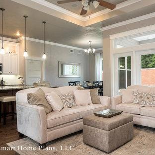 Imagen de sala de estar abierta, de estilo americano, pequeña, con paredes beige y suelo de madera en tonos medios
