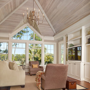 Inspiration for a coastal medium tone wood floor family room remodel in Charleston with beige walls, no fireplace and a media wall
