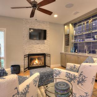 ジャクソンビルの中サイズのビーチスタイルのおしゃれなファミリールーム (ホームバー、グレーの壁、標準型暖炉、石材の暖炉まわり、壁掛け型テレビ、テラコッタタイルの床、赤い床) の写真