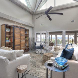 ジャクソンビルの大きいビーチスタイルのおしゃれなファミリールーム (グレーの壁、暖炉なし、内蔵型テレビ、グレーの床、塗装フローリング) の写真