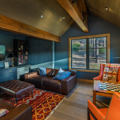 Mountain style enclosed dark wood floor and brown floor game room photo in Sacramento with black walls and a wall-mounted tv