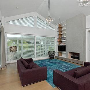 Offenes Modernes Wohnzimmer mit weißer Wandfarbe, hellem Holzboden, Kamin und freistehendem TV in Auckland