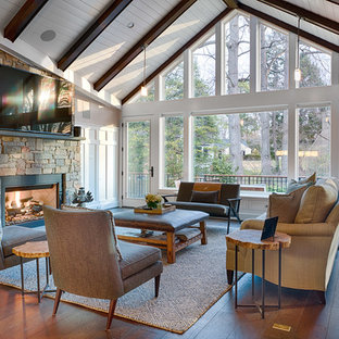 Elegant dark wood floor and brown floor family room photo in DC Metro with gray walls, a standard fireplace, a stone fireplace and a wall-mounted tv