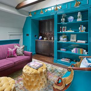 Cette image montre une salle de séjour bohème fermée avec un bar de salon, un mur bleu et un sol en bois foncé.