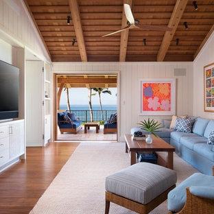 ハワイの大きいトロピカルスタイルのおしゃれなファミリールーム (白い壁、無垢フローリング、暖炉なし、壁掛け型テレビ、茶色い床) の写真