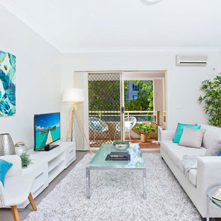 Beach style enclosed family room in Sydney with white walls, carpet, a freestanding tv and grey floor.