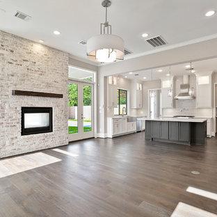 ヒューストンの大きいコンテンポラリースタイルのおしゃれなオープンリビング (グレーの壁、濃色無垢フローリング、両方向型暖炉、レンガの暖炉まわり、壁掛け型テレビ、茶色い床) の写真