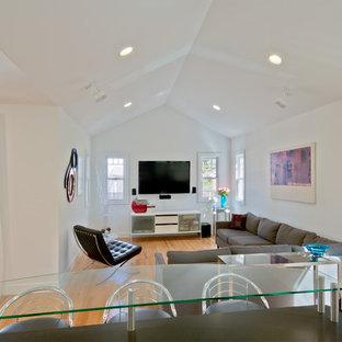 Offenes, Mittelgroßes Modernes Wohnzimmer mit weißer Wandfarbe, braunem Holzboden und Wand-TV in Detroit