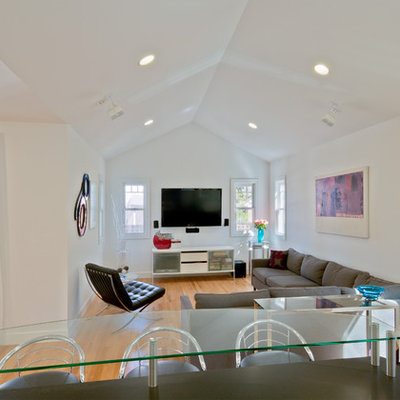 Mid-sized trendy open concept medium tone wood floor family room photo in Detroit with white walls and a wall-mounted tv