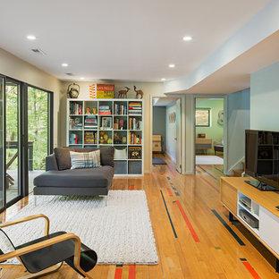 Cette photo montre une salle de séjour tendance avec un téléviseur indépendant, un mur multicolore, un sol en bois clair et un sol marron.