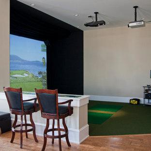 Réalisation d'une très grande salle de séjour champêtre ouverte avec un sol en bois clair, salle de jeu, un mur beige, un téléviseur fixé au mur et un sol vert.