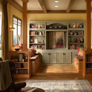 Idee per un soggiorno stile americano con libreria, pareti gialle, pavimento in legno massello medio, nessuna TV e pavimento marrone