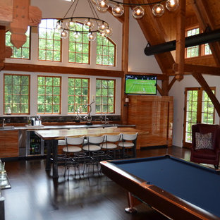 Game room - large contemporary enclosed dark wood floor and brown floor game room idea in New York with white walls, a standard fireplace, a stone fireplace and a tv stand