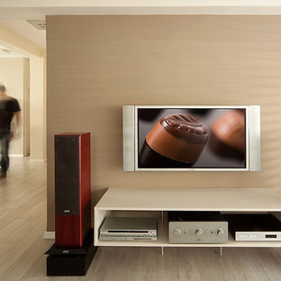 Inspiration for a contemporary light wood floor family room remodel in Other with beige walls and a wall-mounted tv