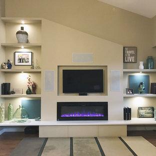 バンクーバーの小さいトランジショナルスタイルのおしゃれなオープンリビング (ベージュの壁、ラミネートの床、吊り下げ式暖炉、埋込式メディアウォール) の写真