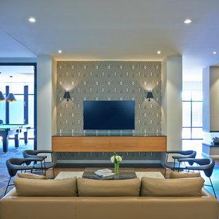 Idee per un soggiorno di medie dimensioni e aperto con sala giochi, pareti multicolore, pavimento in legno massello medio, camino bifacciale, cornice del camino in intonaco e TV a parete