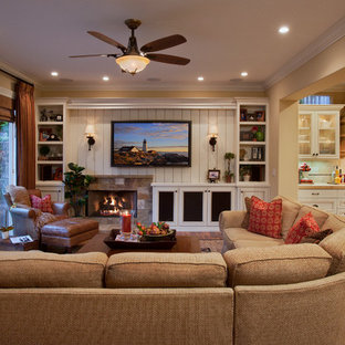 Design ideas for a large traditional open concept family room in Orange County with beige walls, medium hardwood floors, a standard fireplace, a stone fireplace surround, a wall-mounted tv and brown floor.