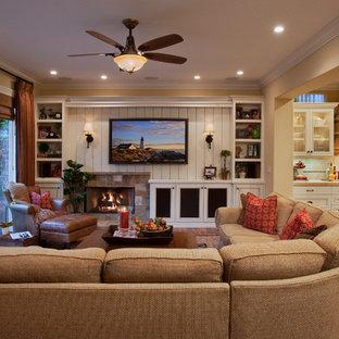 Offenes, Großes Klassisches Wohnzimmer mit beiger Wandfarbe, braunem Holzboden, Kamin, Kaminsims aus Stein, Wand-TV und braunem Boden in Orange County