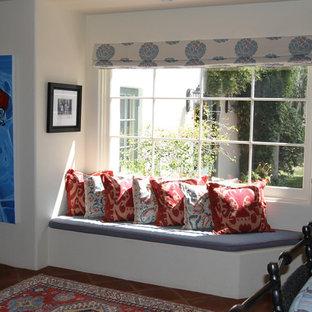 Idee per un soggiorno mediterraneo di medie dimensioni e aperto con libreria, pareti beige, pavimento in terracotta, camino classico, cornice del camino piastrellata e TV a parete