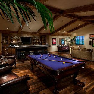 Diseño de sala de juegos en casa mediterránea, grande, con paredes beige, televisor colgado en la pared y suelo de madera oscura