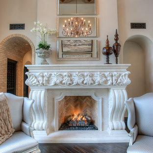 Réalisation d'une très grande salle de séjour avec une bibliothèque ou un coin lecture méditerranéenne ouverte avec un mur beige, un sol en bois foncé, une cheminée standard, un manteau de cheminée en pierre, aucun téléviseur et un sol marron.