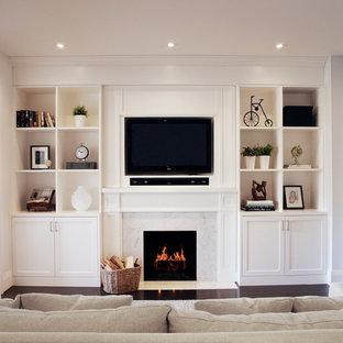 Modelo de sala de estar tradicional renovada con suelo de madera oscura, chimenea tradicional y televisor colgado en la pared
