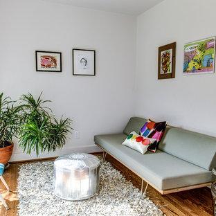 Modernes Wohnzimmer mit weißer Wandfarbe und braunem Holzboden in Houston