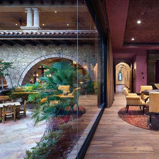 Ispirazione per un soggiorno mediterraneo chiuso con sala giochi, pareti viola e TV a parete