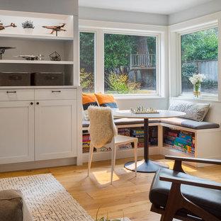 Cette photo montre une salle de séjour chic de taille moyenne et ouverte avec salle de jeu, un mur gris, un sol en bois clair, un poêle à bois, un manteau de cheminée en brique, un téléviseur fixé au mur et un sol marron.