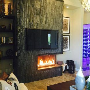 Foto di un soggiorno classico di medie dimensioni e chiuso con camino bifacciale, cornice del camino piastrellata, pareti beige, pavimento in gres porcellanato, TV a parete e pavimento beige