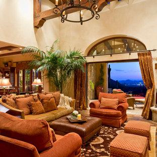 フェニックスの巨大なサンタフェスタイルのおしゃれなオープンリビング (ベージュの壁、無垢フローリング、コーナー設置型暖炉、レンガの暖炉まわり) の写真