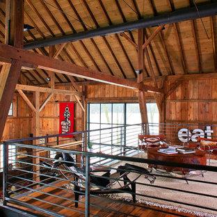 Réalisation d'une salle de séjour mansardée ou avec mezzanine champêtre avec un sol en bois brun.