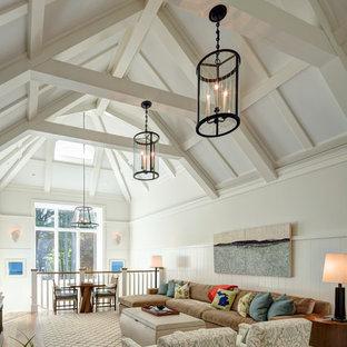 グランドラピッズの大きいビーチスタイルのおしゃれなファミリールーム (白い壁、無垢フローリング、暖炉なし、茶色い床) の写真