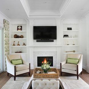 Diseño de sala de estar cerrada, campestre, de tamaño medio, con paredes blancas, suelo de madera en tonos medios, chimenea tradicional, marco de chimenea de baldosas y/o azulejos y televisor colgado en la pared