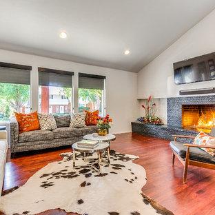オクラホマシティの大きいエクレクティックスタイルのおしゃれなファミリールーム (無垢フローリング、標準型暖炉、レンガの暖炉まわり、壁掛け型テレビ) の写真
