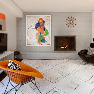 シャーロットの中サイズのミッドセンチュリースタイルのおしゃれなファミリールーム (濃色無垢フローリング、標準型暖炉、レンガの暖炉まわり、グレーの壁、据え置き型テレビ) の写真