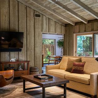 Ejemplo de sala de estar cerrada, vintage, pequeña, con paredes grises, suelo de cemento, chimenea tradicional, marco de chimenea de ladrillo, televisor colgado en la pared y suelo marrón