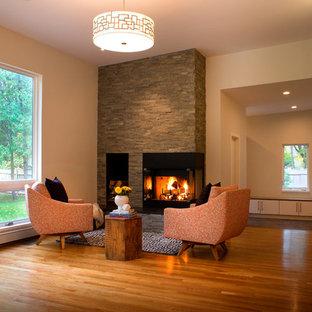 Imagen de sala de estar abierta, retro, de tamaño medio, con paredes blancas, suelo de madera clara, chimenea de esquina y marco de chimenea de piedra