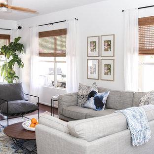 フェニックスの中サイズのミッドセンチュリースタイルのおしゃれなファミリールーム (白い壁、濃色無垢フローリング、標準型暖炉、木材の暖炉まわり、壁掛け型テレビ、茶色い床) の写真
