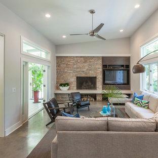 ウィルミントンの中サイズのミッドセンチュリースタイルのおしゃれなファミリールーム (グレーの壁、コンクリートの床、石材の暖炉まわり、標準型暖炉、壁掛け型テレビ) の写真