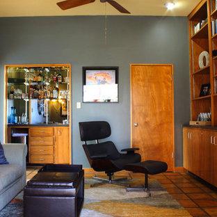 Foto de sala de estar cerrada, retro, de tamaño medio, con paredes grises, suelo de baldosas de terracota, pared multimedia y suelo marrón