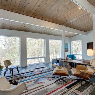 グランドラピッズの中くらいのミッドセンチュリースタイルのおしゃれなオープンリビング (白い壁、スレートの床、壁掛け型テレビ、暖炉なし、グレーの床) の写真
