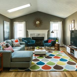 Mittelgroßes, Offenes Retro Wohnzimmer mit grauer Wandfarbe, braunem Holzboden, Kamin, gefliester Kaminumrandung und freistehendem TV in Providence