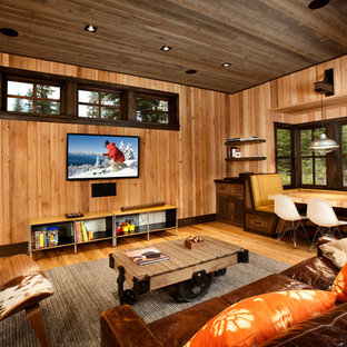 Mountain style medium tone wood floor and brown floor family room photo with brown walls and a wall-mounted tv