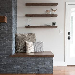 シアトルの大きいミッドセンチュリースタイルのおしゃれなファミリールーム (白い壁、濃色無垢フローリング、標準型暖炉、タイルの暖炉まわり、内蔵型テレビ、茶色い床) の写真