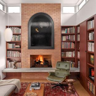 Immagine di un soggiorno minimalista di medie dimensioni e aperto con libreria, pareti bianche, pavimento in sughero, camino classico, cornice del camino in mattoni, nessuna TV, pavimento marrone e soffitto in perlinato