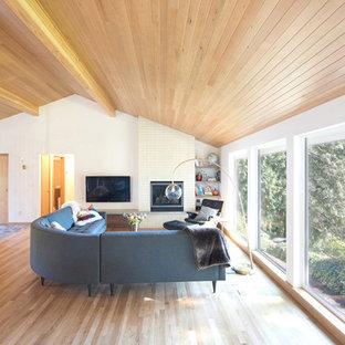 シアトルの中くらいのミッドセンチュリースタイルのおしゃれなオープンリビング (無垢フローリング、標準型暖炉、タイルの暖炉まわり、壁掛け型テレビ、茶色い床、白い壁) の写真